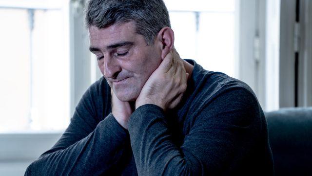 older man holding his neck
