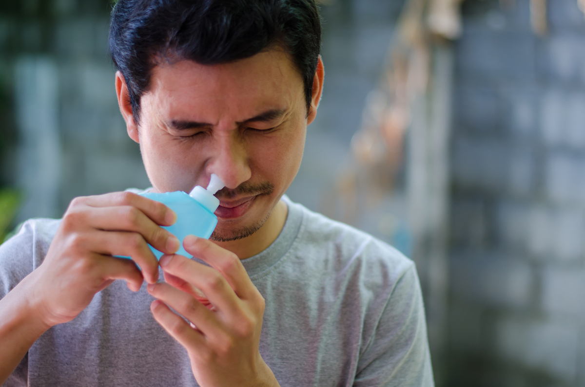 asian man uses saline to clean sinuses