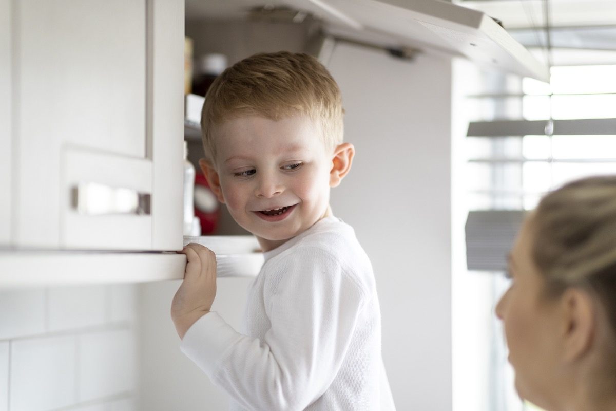 A shot of a mother and her son in the kitchen, the young boy is reaching in the cupboard.
