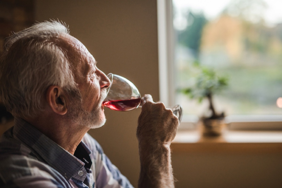 Pensive senior man drinking red wine at home and looking away