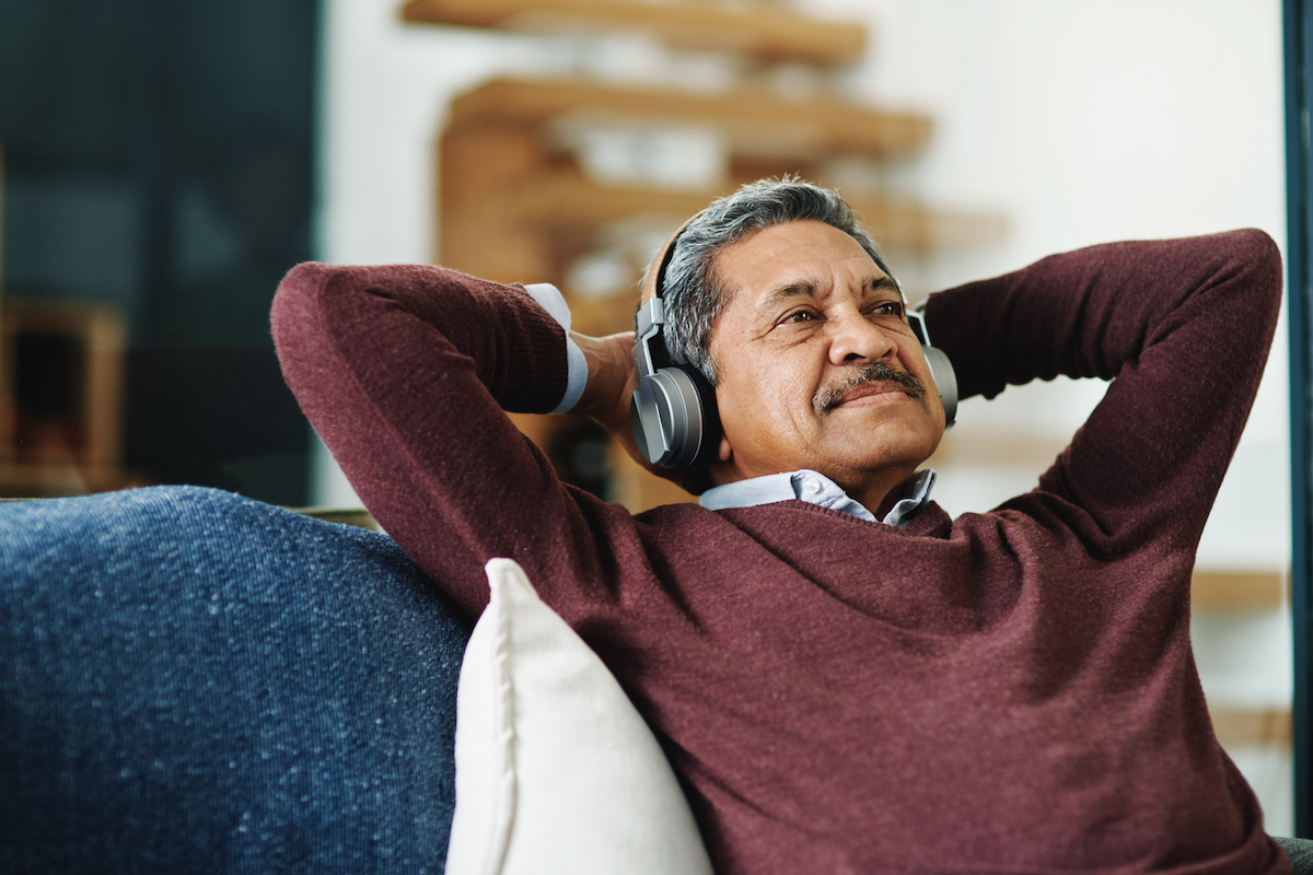 senior man of color listening to music on couch with his hands behind his head