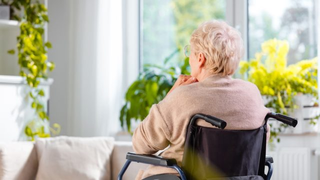 Rear view shot of a senior woman sitting in wheelchair and thinking
