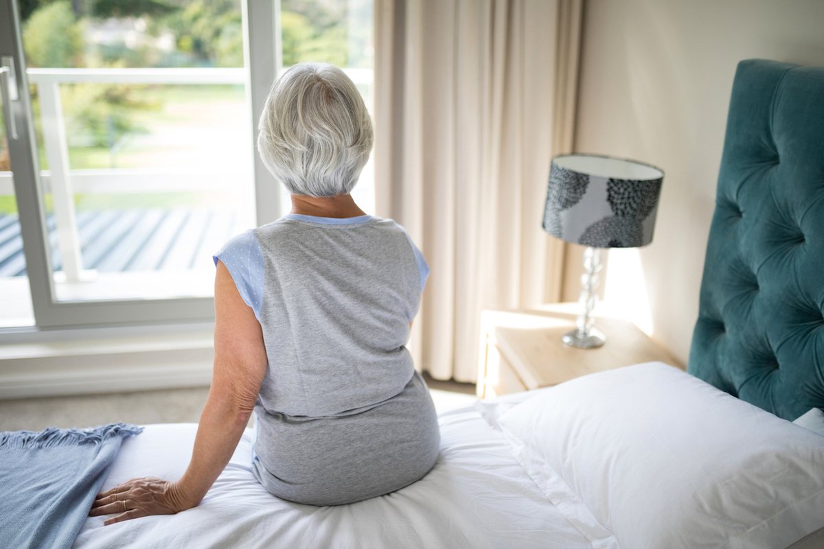 Rear view of senior woman sitting on bed in bedroom, looking out window
