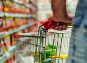 closeup of white man's arm holding on to cart in grocery store