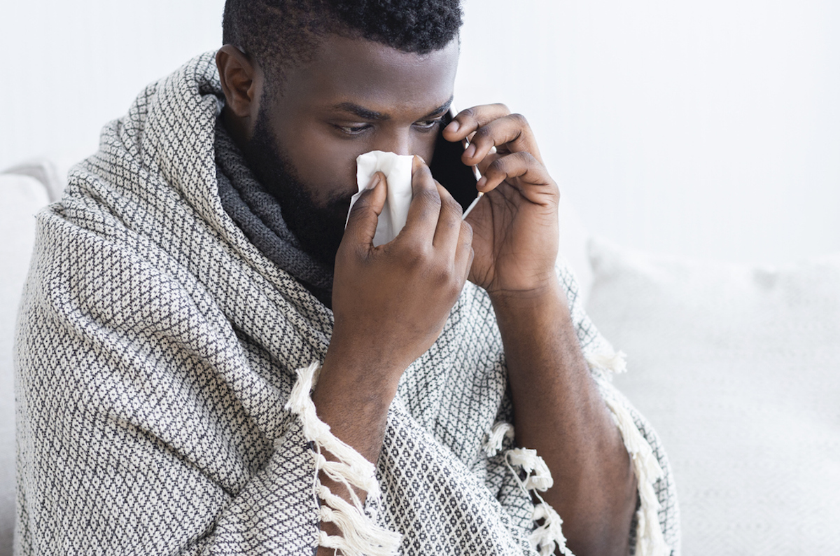 sick black man talking to doctor on phone while blowing his nowse