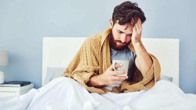 sick man sits in bed with tea