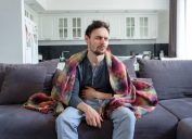 A young sick white man sits on a sofa in blankets and holds his stomach