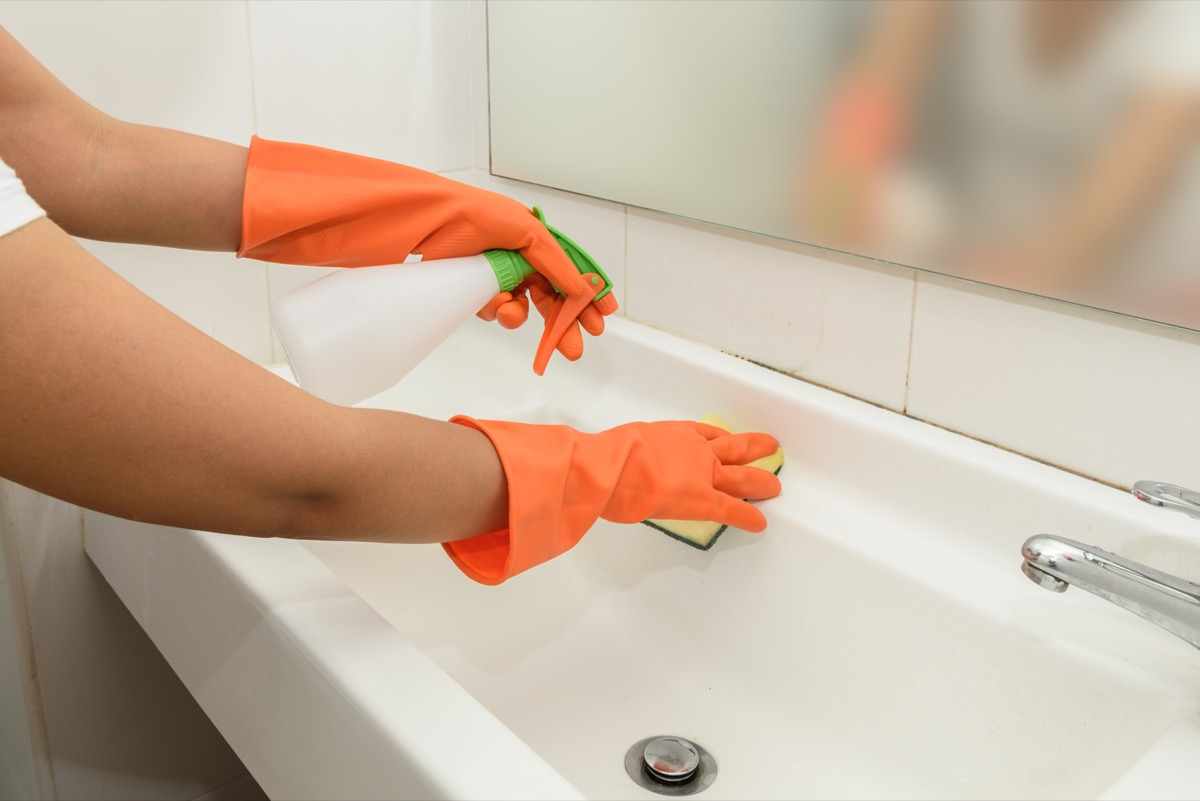 Woman wiping down sink