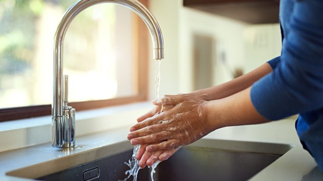 Shot of an unrecognizable woman washing her hands in the kitchen sink