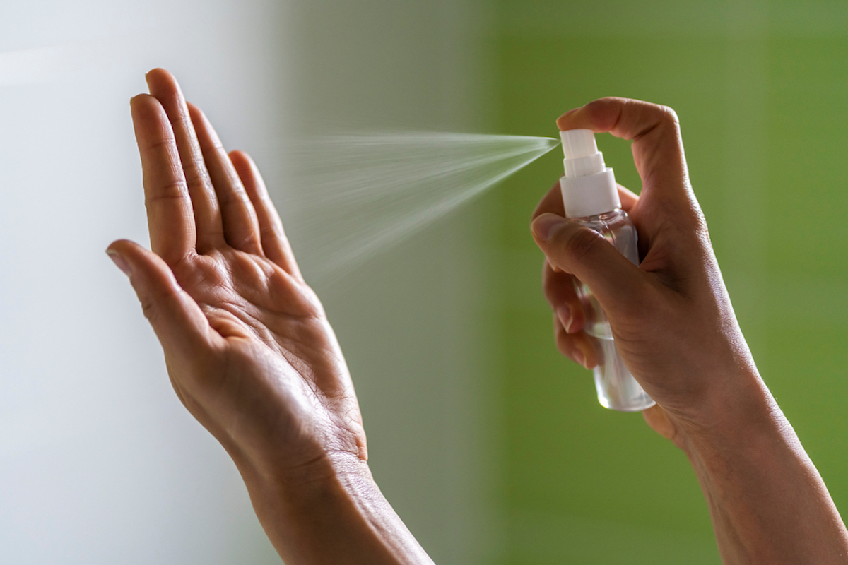 woman's hand sprays from spray bottle onto other hand