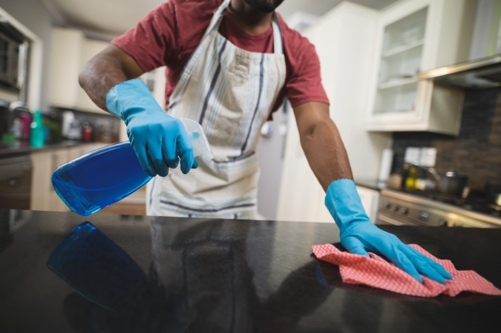 Mid section man cleaning black marble counter in kitchen at home