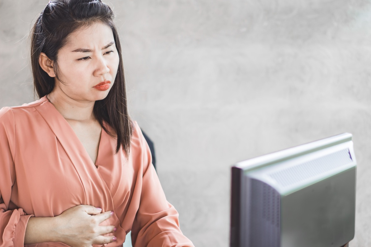 Woman experiencing stomach discomfort while working on computer
