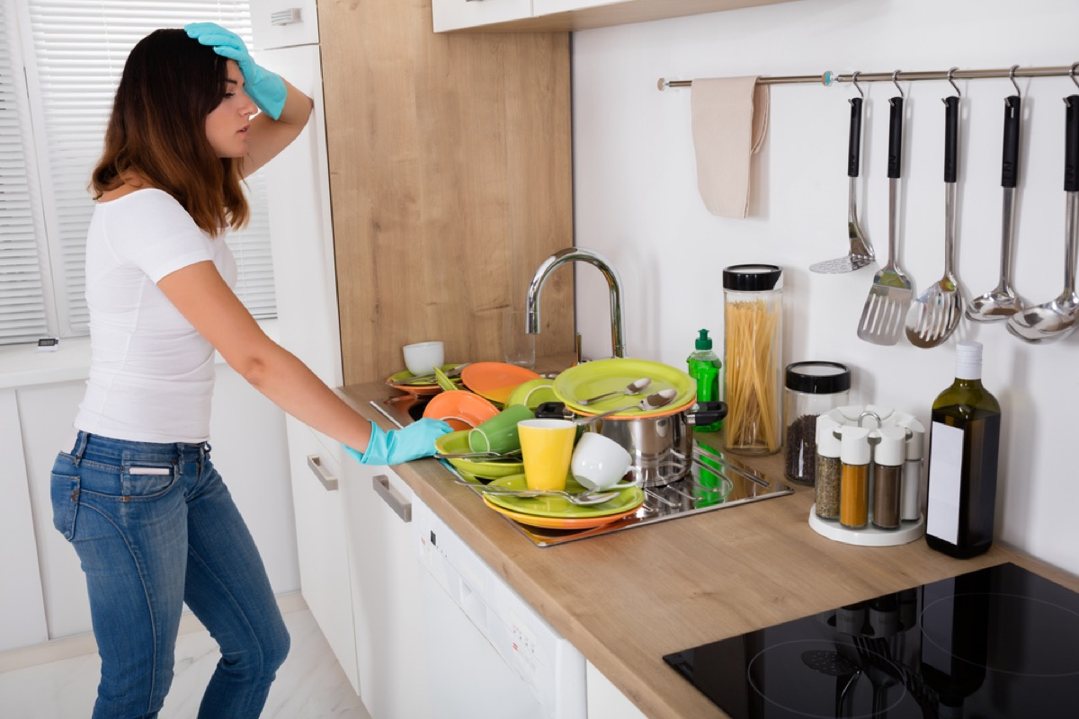 stressed woman looking at dirty dishes