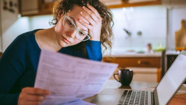 Young brunette curly female reading her bill papers, looking stressed