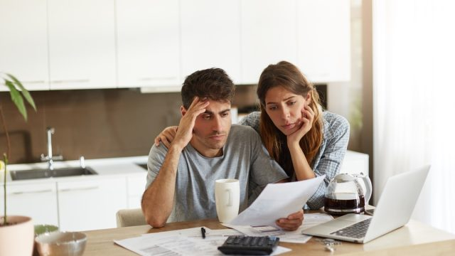 Stressed couple looking at paperwork