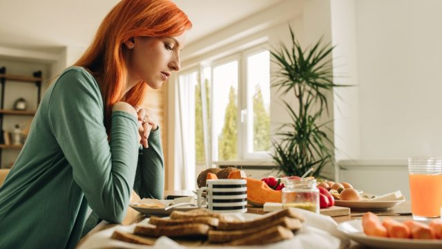 Lonely redhead woman sitting at dining table and thinking of something.