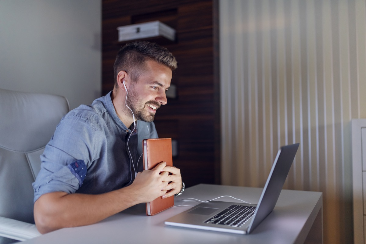 Handsome bearded employee holding agenda in hands, having video call over laptop and sitting in office late at night.
