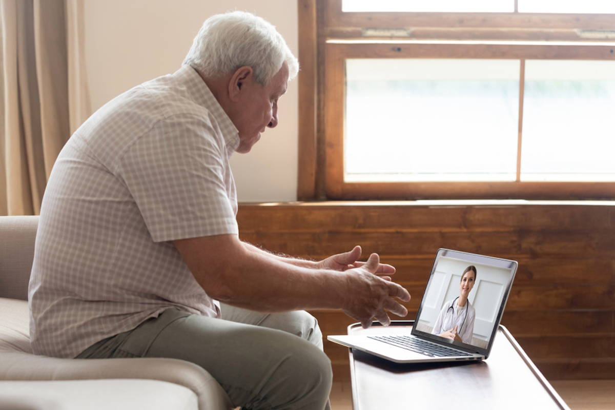 senior man sits on couch talking to doctor via laptop in telehealth appointment