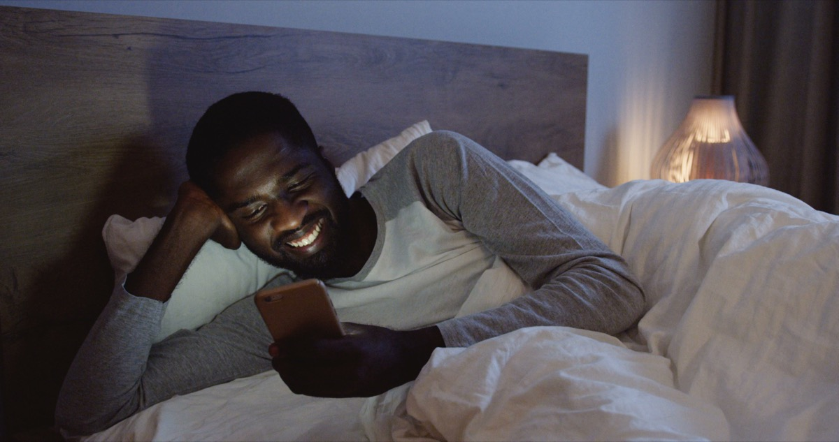 Man texting in bed not sleeping at night