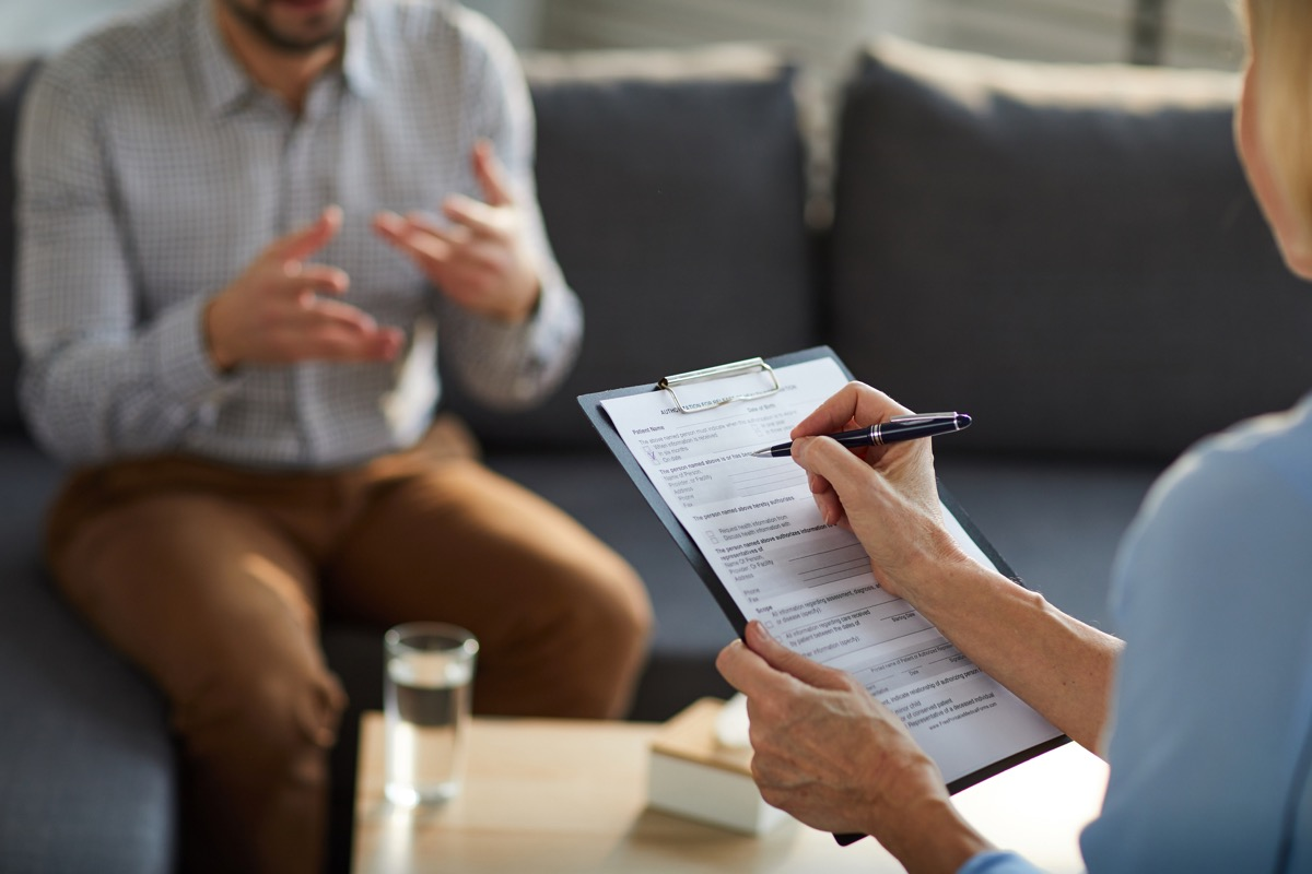 Mature professional counselor filling in document while having discussion with patient in trouble