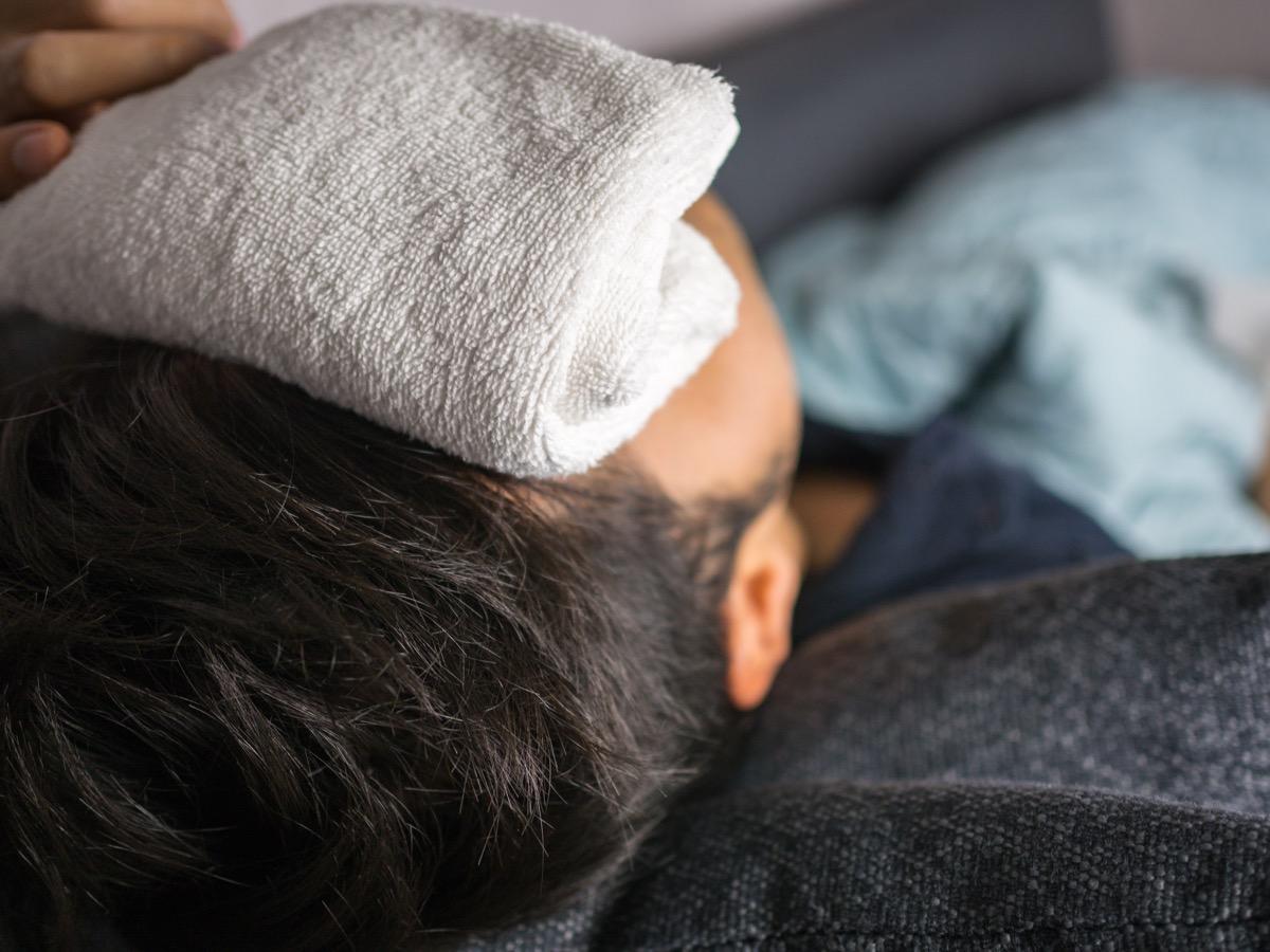 Towel on forehead, on man feels sick