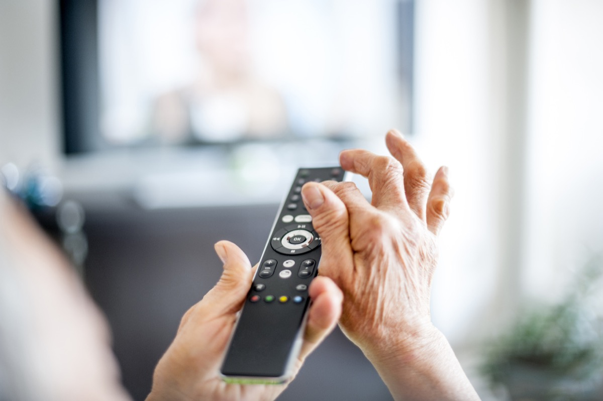 Close Up Hands Of Senior Woman Using TV Remote Control