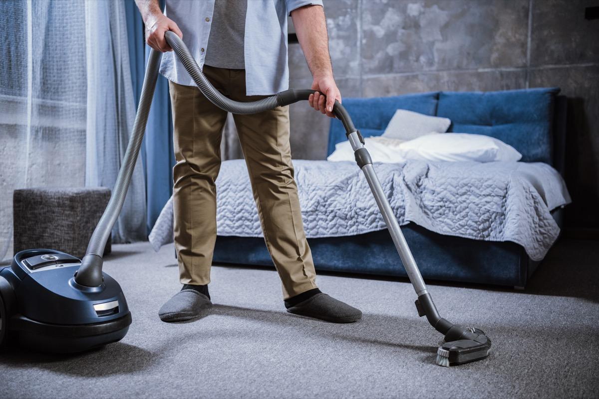 Man vacuuming bedroom carpet