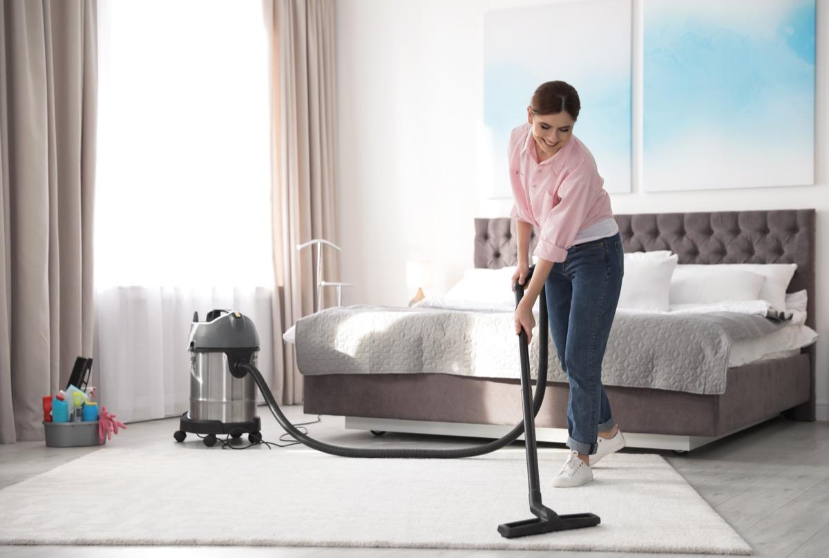Woman vacuuming bedroom carpet