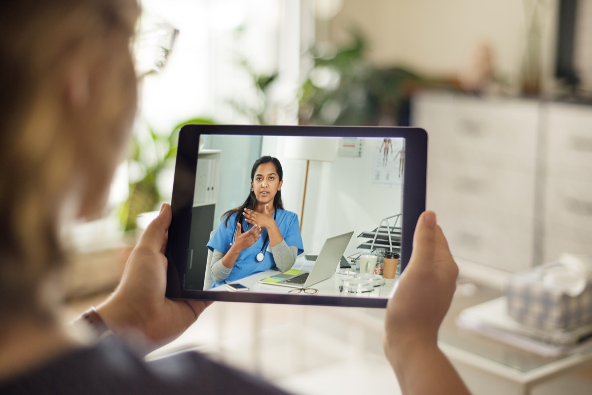 Over the shoulder shot of a patient talking to a doctor using of a digital tablet
