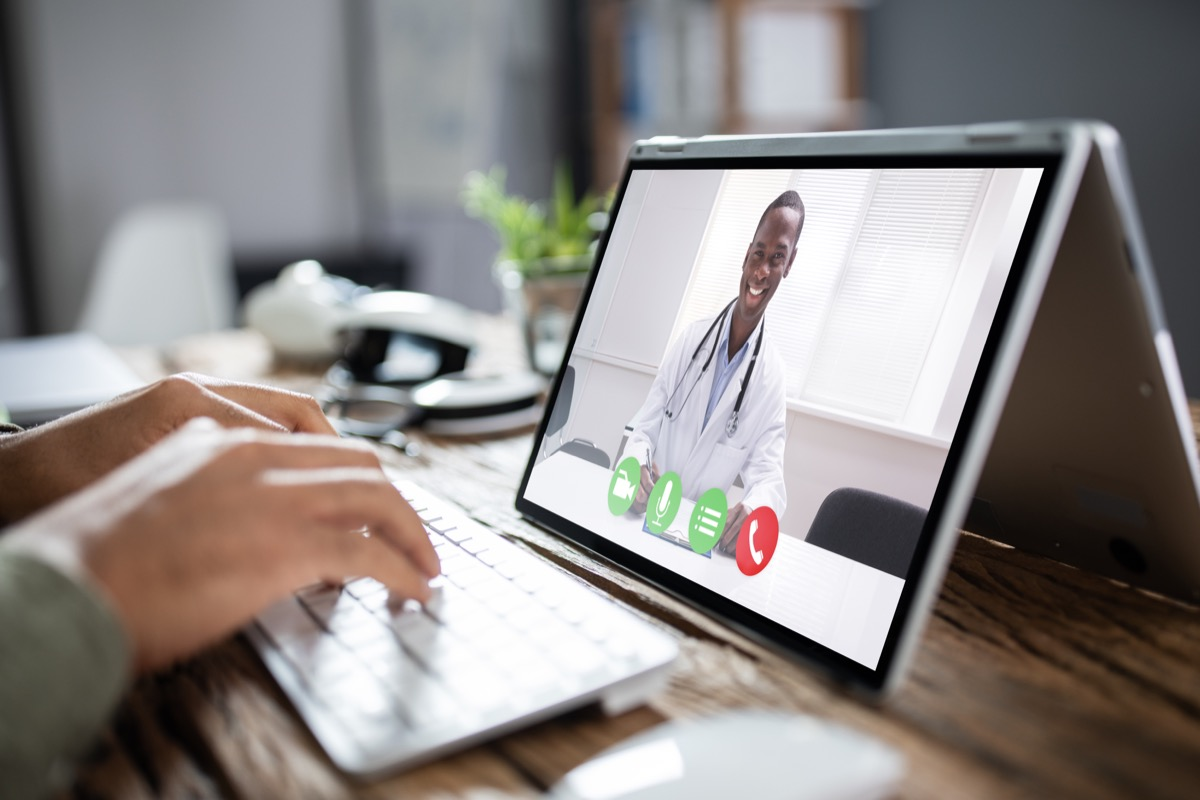 Young Male Doctor Video Chatting On Laptop In Clinic