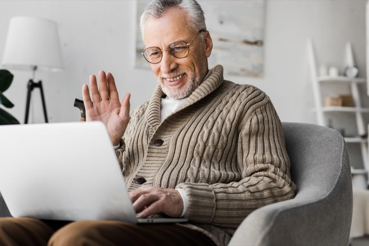 cheerful senior man in glasses waving hand while having video call