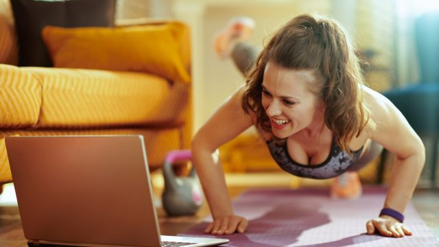 smiling healthy woman in fitness clothes in the modern living room watching fitness tutorial on internet via laptop and doing pushups on fitness mat. (smiling healthy woman in fitness clothes in the modern living room watching fitness tutorial on inte