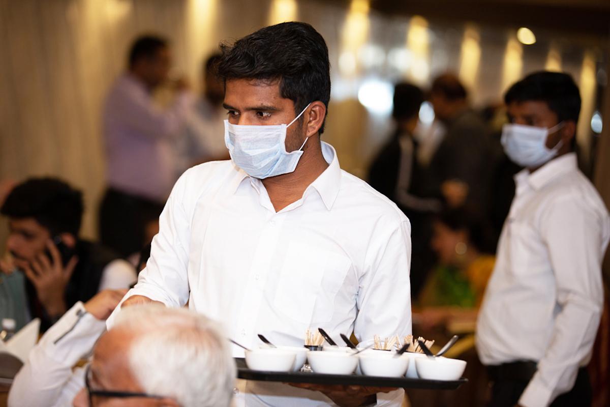 waiter wears mask at event, handling food