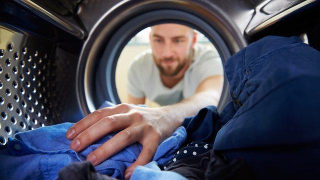 man washing his blue laundry
