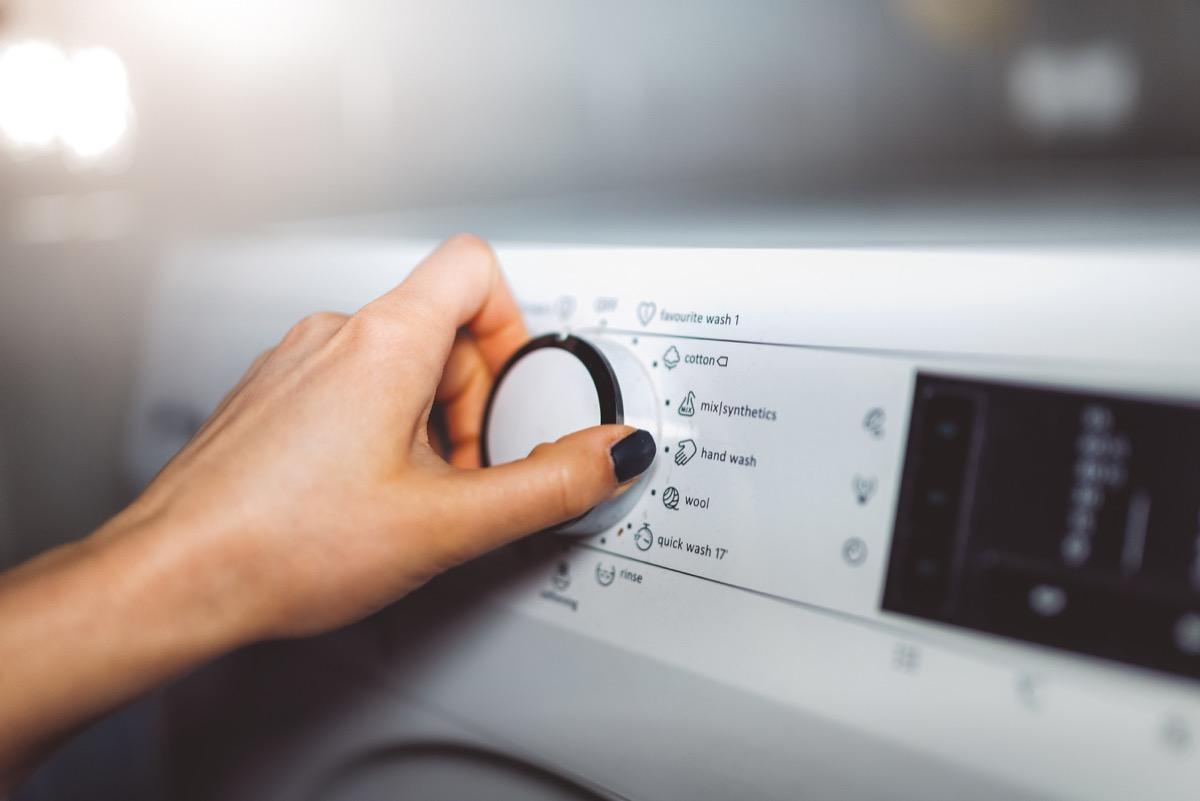 woman choosing washing cycle