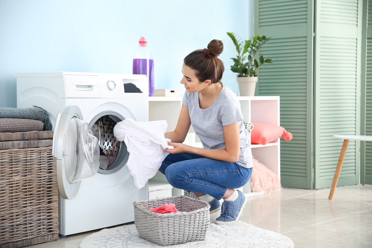 Woman putting linens in washing machine laundry room