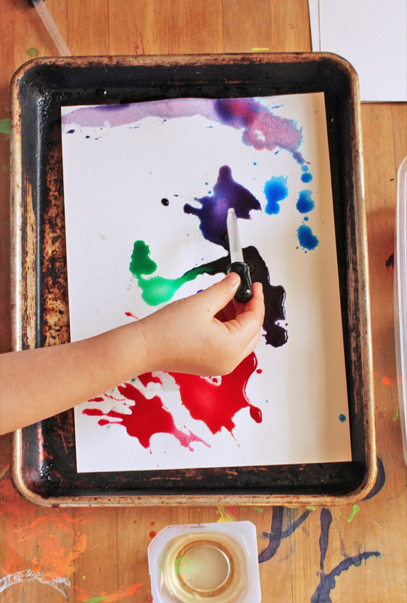 kid dropping paint on paper with eye dropper