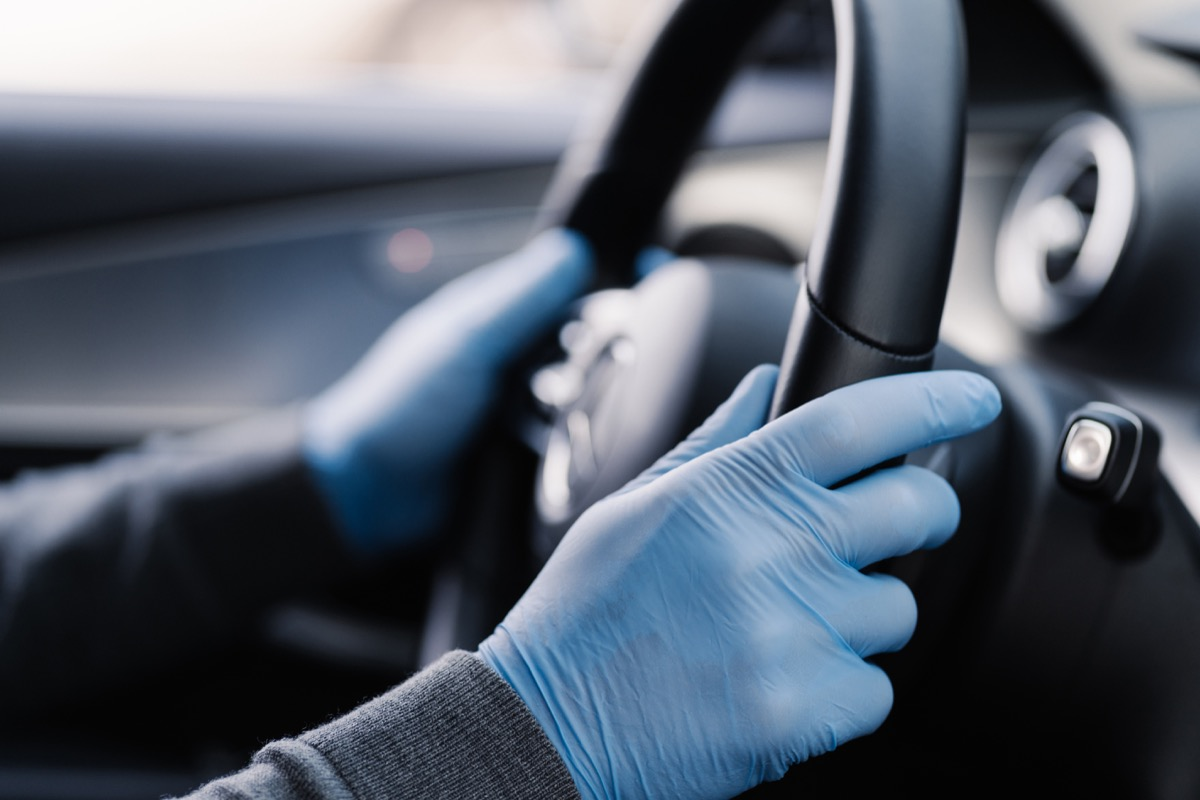 hands in blue gloves holding steering wheel