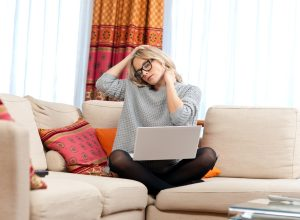 Woman with neck pain working on couch with laptop