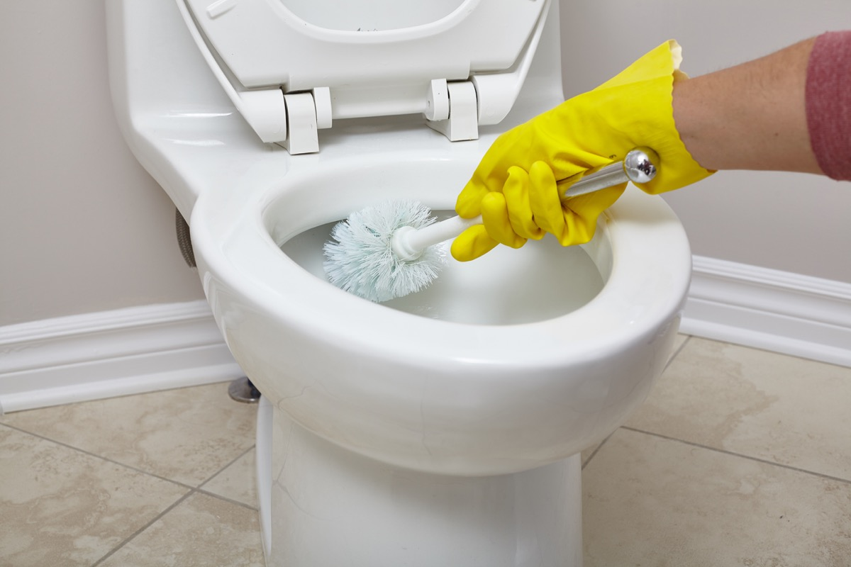 white hand cleaning toilet with toilet brush