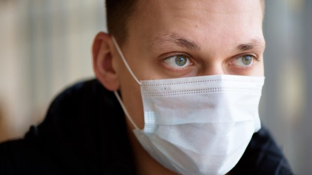 young white man wearing surgical mask