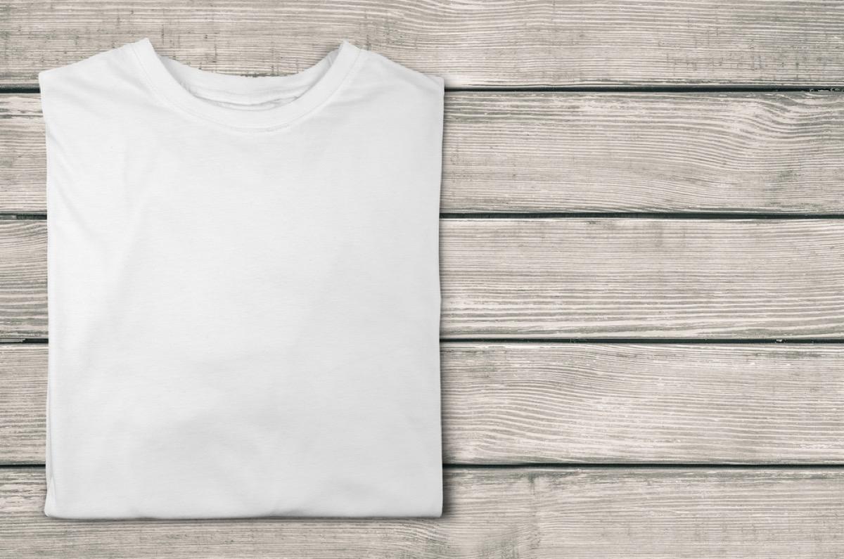 white t-shirt folded on wood background