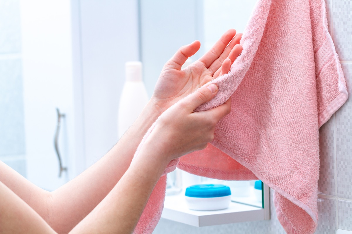 white woman drying hand on pink hand towel