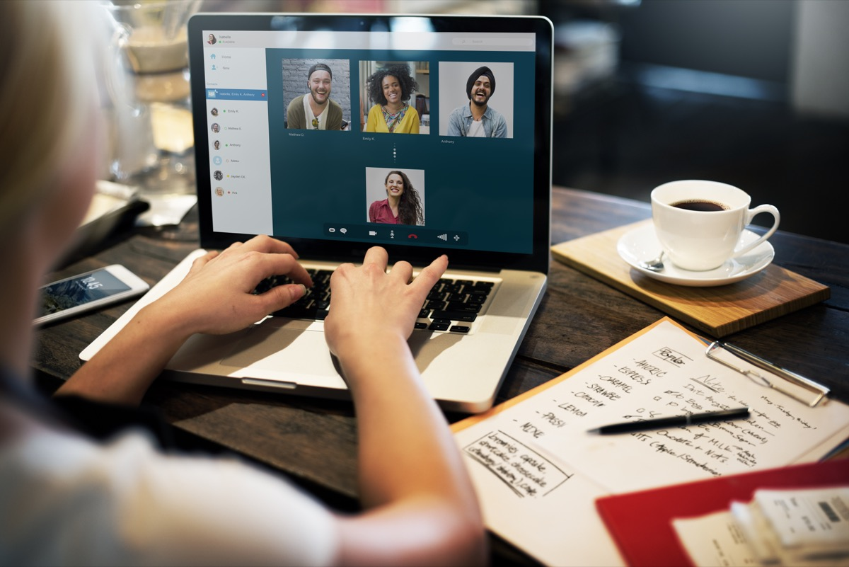 young white woman typing in chat function on video call while wfh