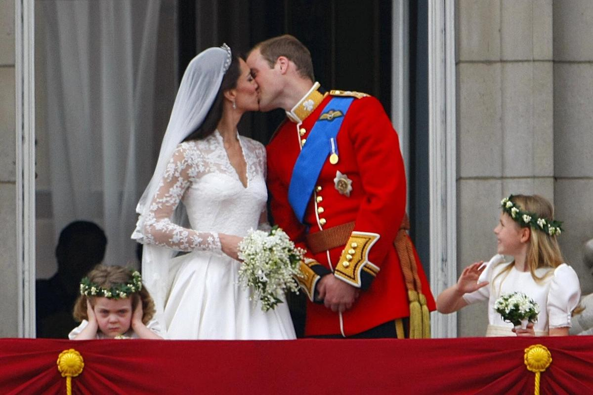 Prince William and his wife Kate Middleton kissing on the balcony of Buckingham Palace, London watched by bridesmaids Margarita Armstrong-Jones (right) and Grace Van Cutsem (left), following their wedding at Westminster Abbey in April 2011
