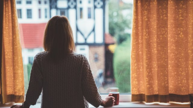 Rear view of woman at home staring through the window