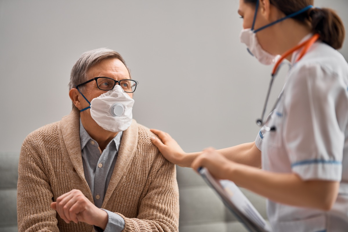 young doctor or nurse taking care of elderly white man with coronavirus