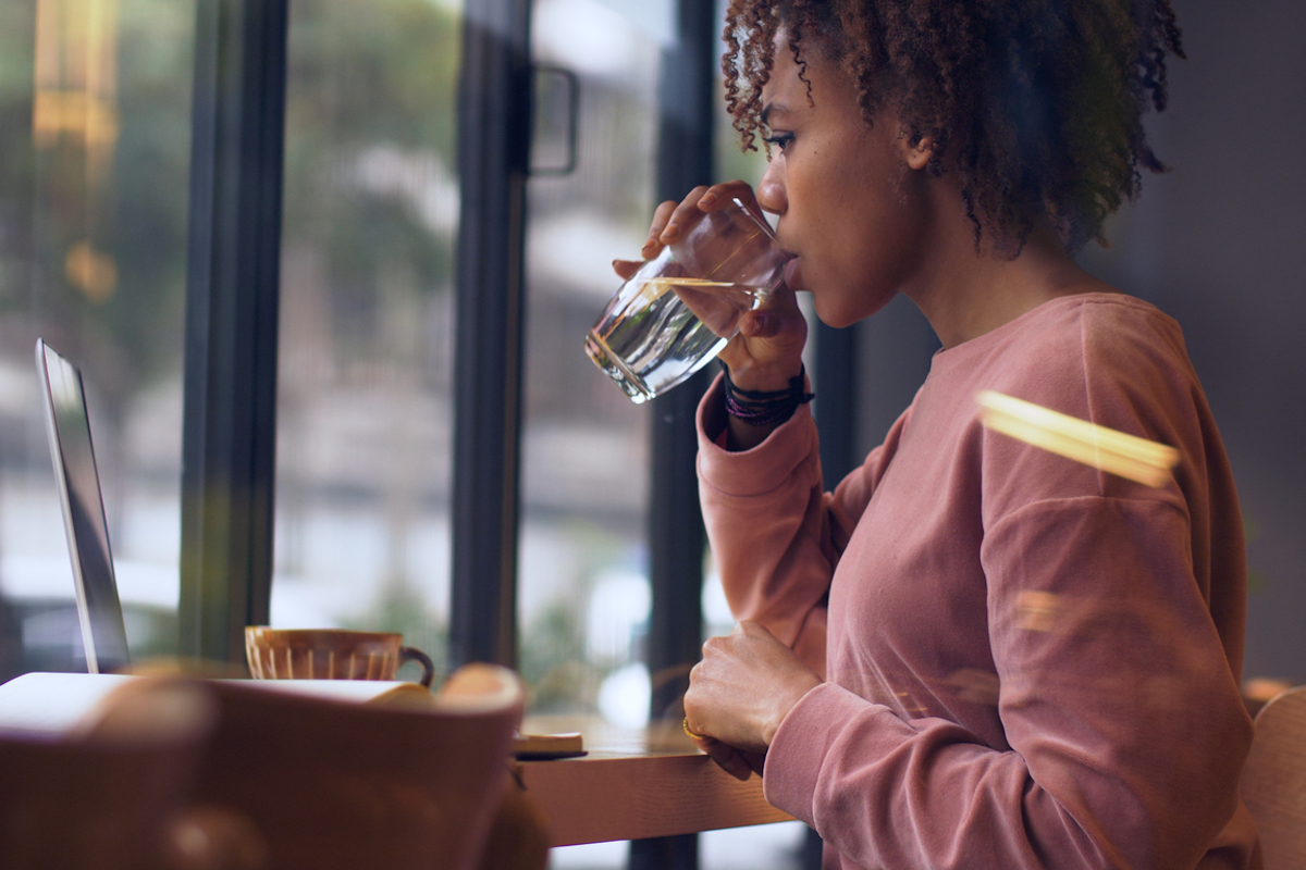 black woman sitting at table on laptop drinking water