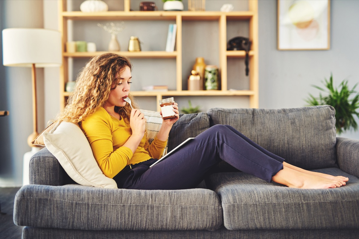 Shot of a young woman eating chocolate from a jar while relaxing on the sofa at home