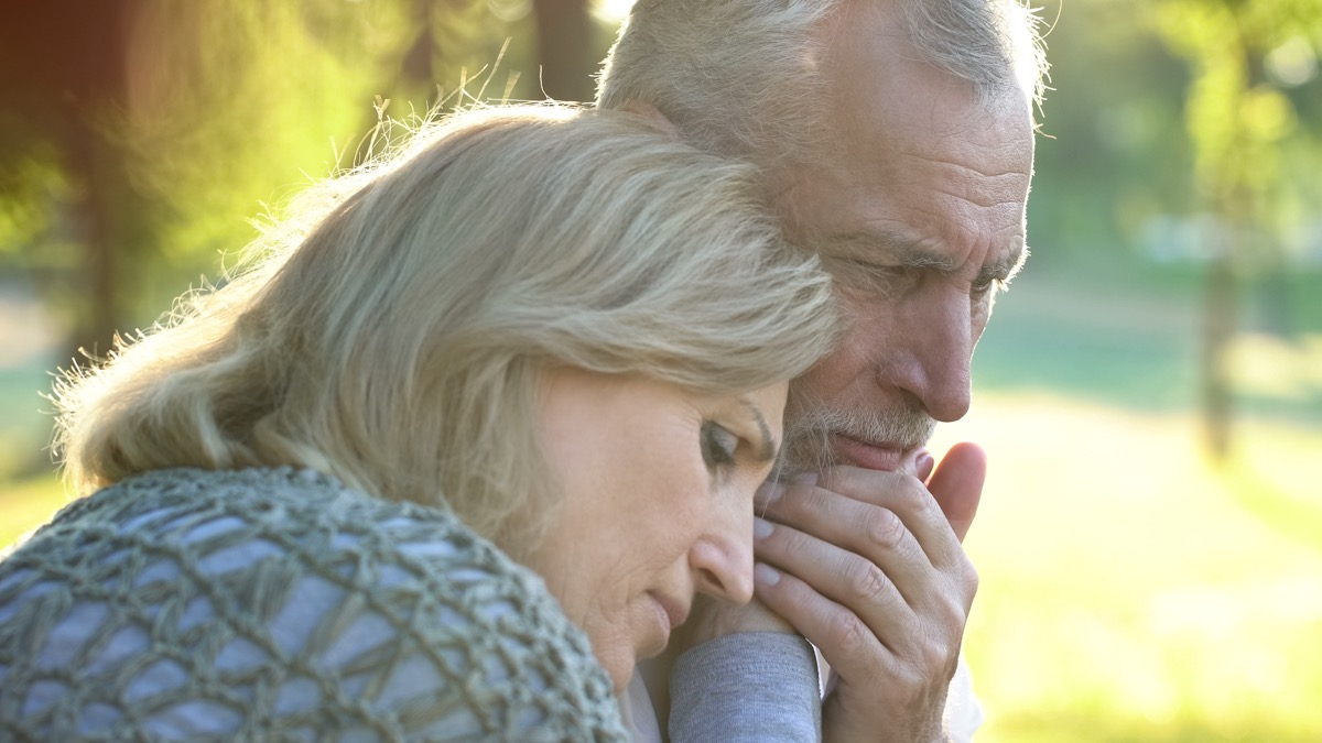Retired woman embracing ill husband, support and care, family togetherness
